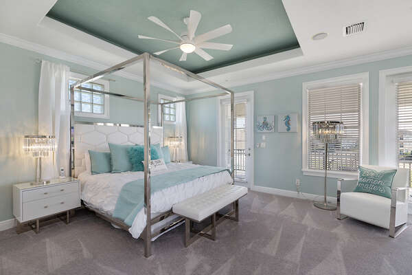 The master suite with a luxury king bed and private access to the third-floor balcony