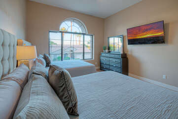 Bedroom 2 has a TV, ceiling fan and neighborhood views from end windows.