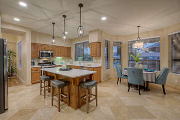 Open, spacious and naturally bright kitchen with bar and table seating options.