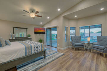 Primary suite features a king bed, TV, walk-in closet, ceiling fan and covered balcony.