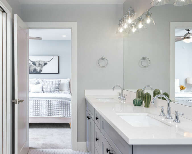 Private bathroom with dual vanities and luxurious shower.
