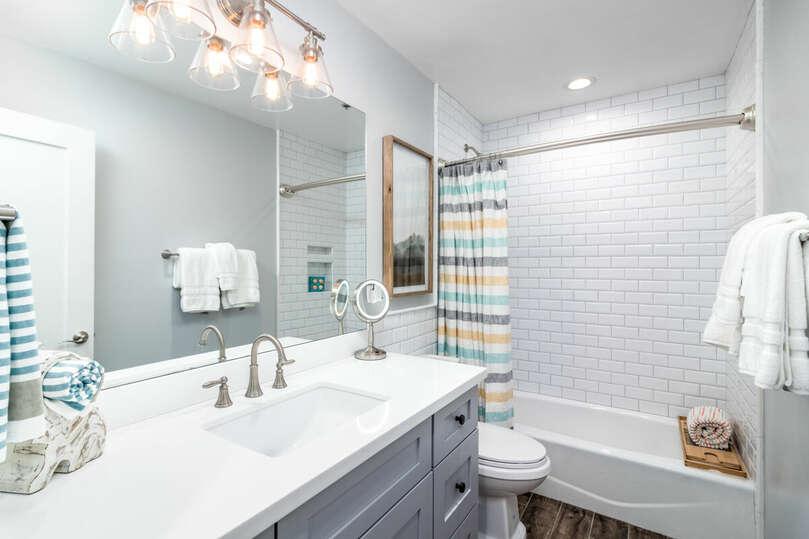 Second, a modern bathroom with a combination shower, bathtub.
