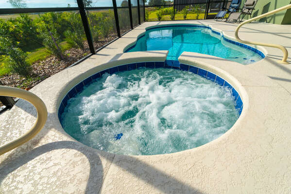 Hot tub and pool with grassy view