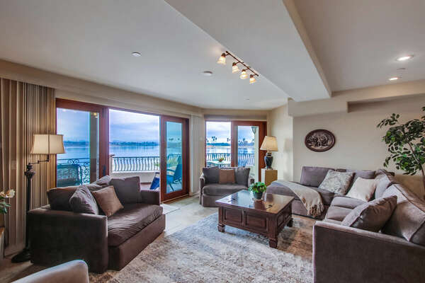 Living Room with Fireplace, TV, and Entrance to Bayfront Deck