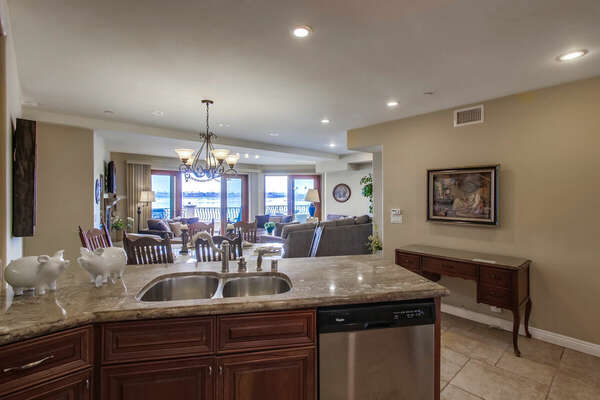 View from the Fully Equipped Kitchen Across the Dining and Living Areas