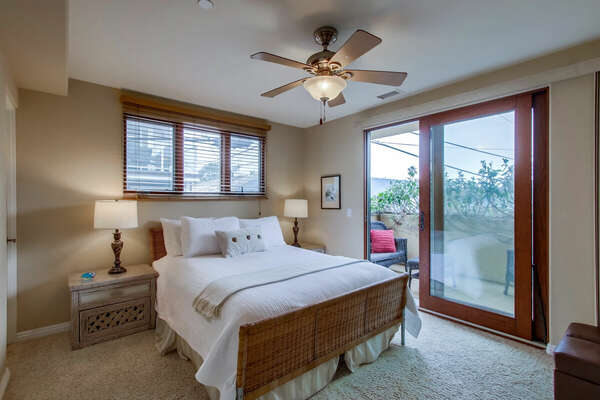 Guest Bedroom with a Queen Bed and Entrance to Deck