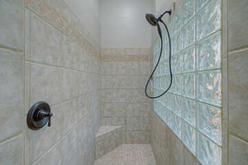 Feel clean and relaxed after rinsing off in the primary suite's walk-in shower