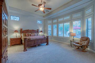 Primary suite features a king bed, ceiling fan and a wall of windows for viewing the backyard oasis