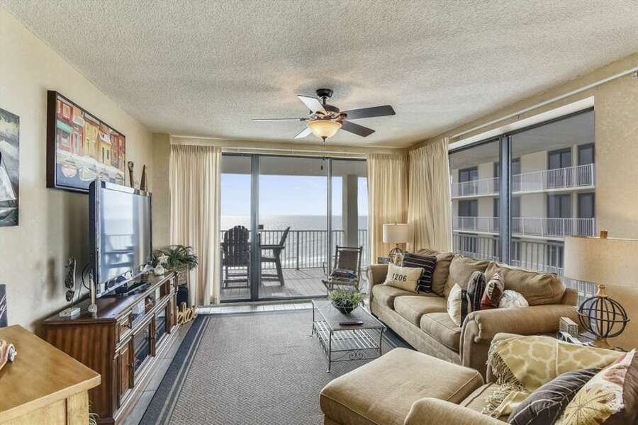 Warmly Updated Living Room with Floor to Ceiling Windows and Access to Private Balcony