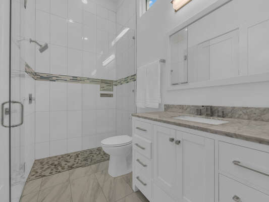 The bathroom has a tub/shower combination and a beautiful marble counter top