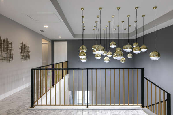 Gaze in awe at the custom light fixtures over the staircase