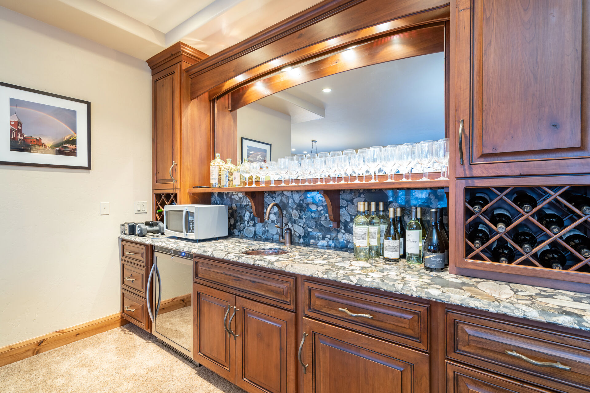 Private wet bar with plenty of glasses and drink options.