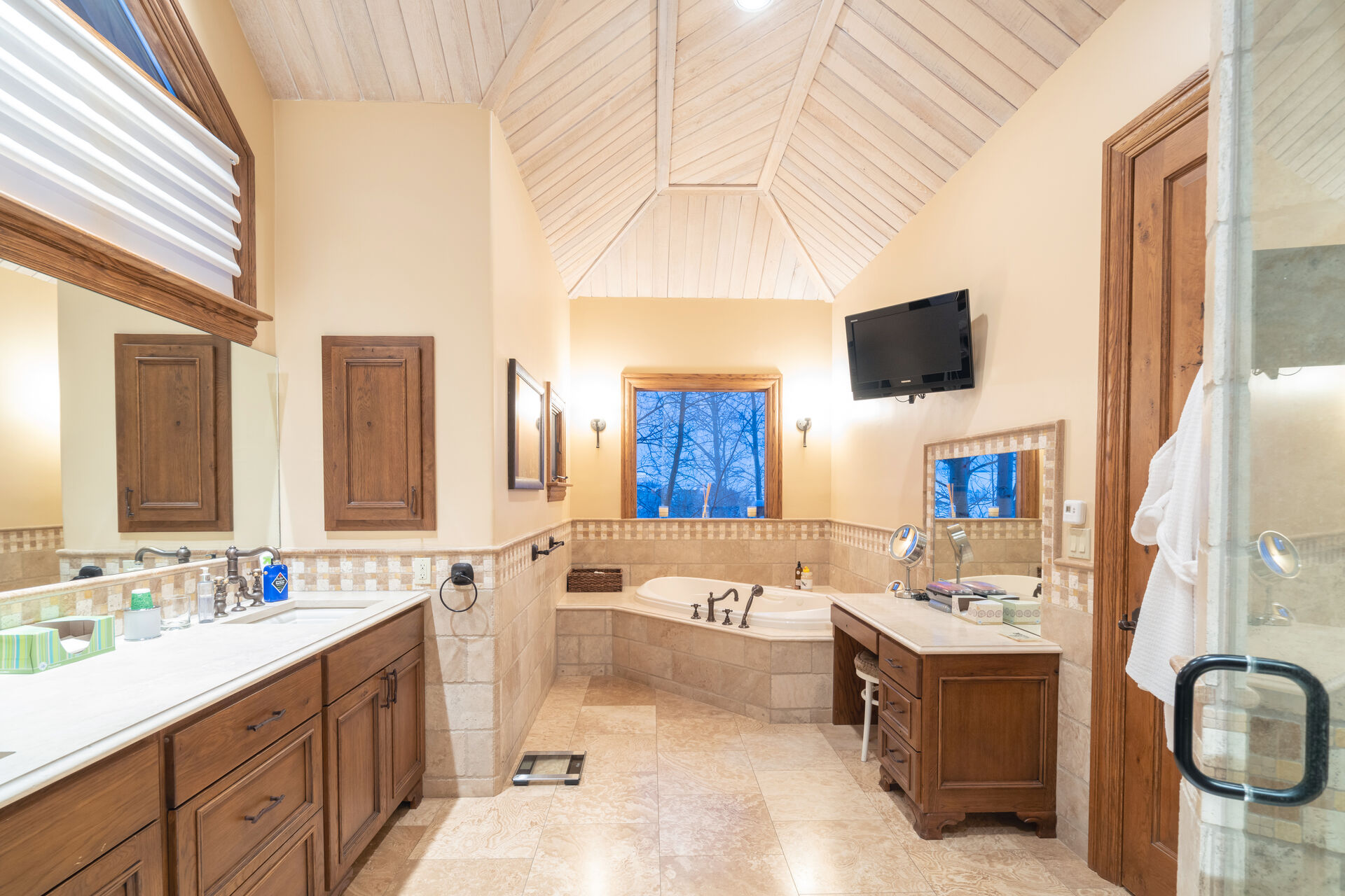 Bathroom with spa tub, vanity sinks, and wall-mounted TV.