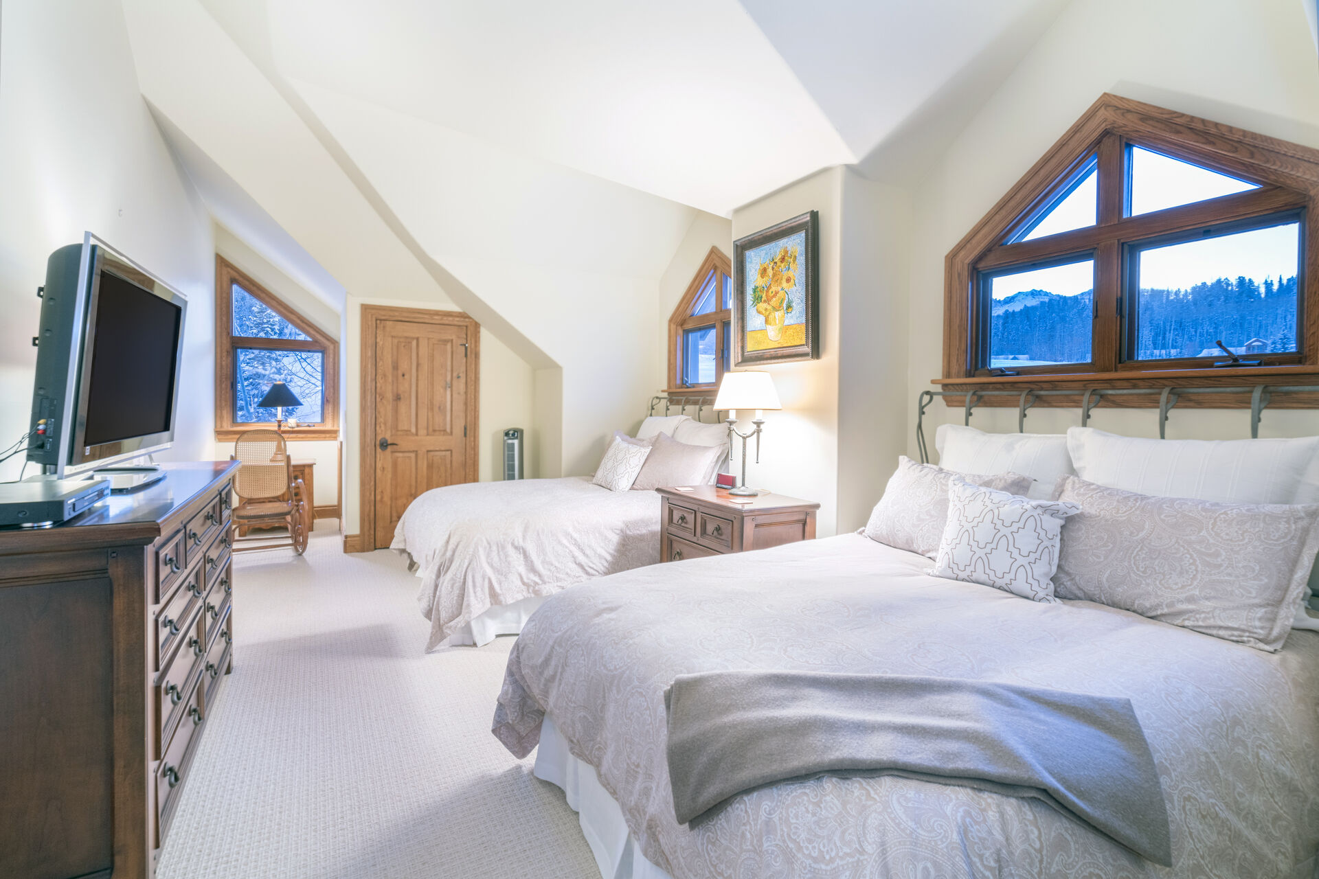 Another one of the bedrooms, complete with two large beds, a nightstand in between, and a wall-mounted TV above a dresser.