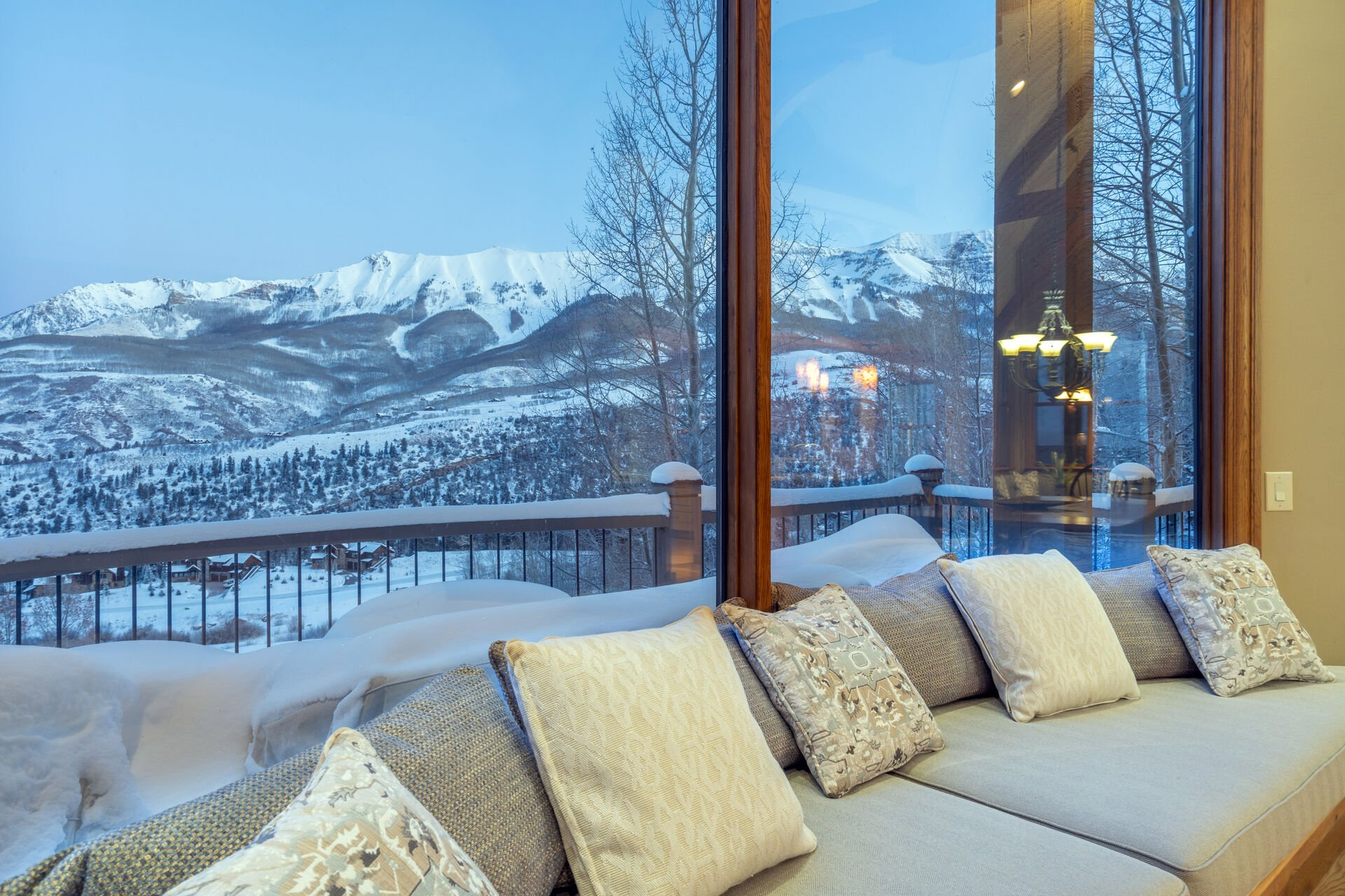 Large windows behind a long cushioned bench look out onto a snowy landscape.