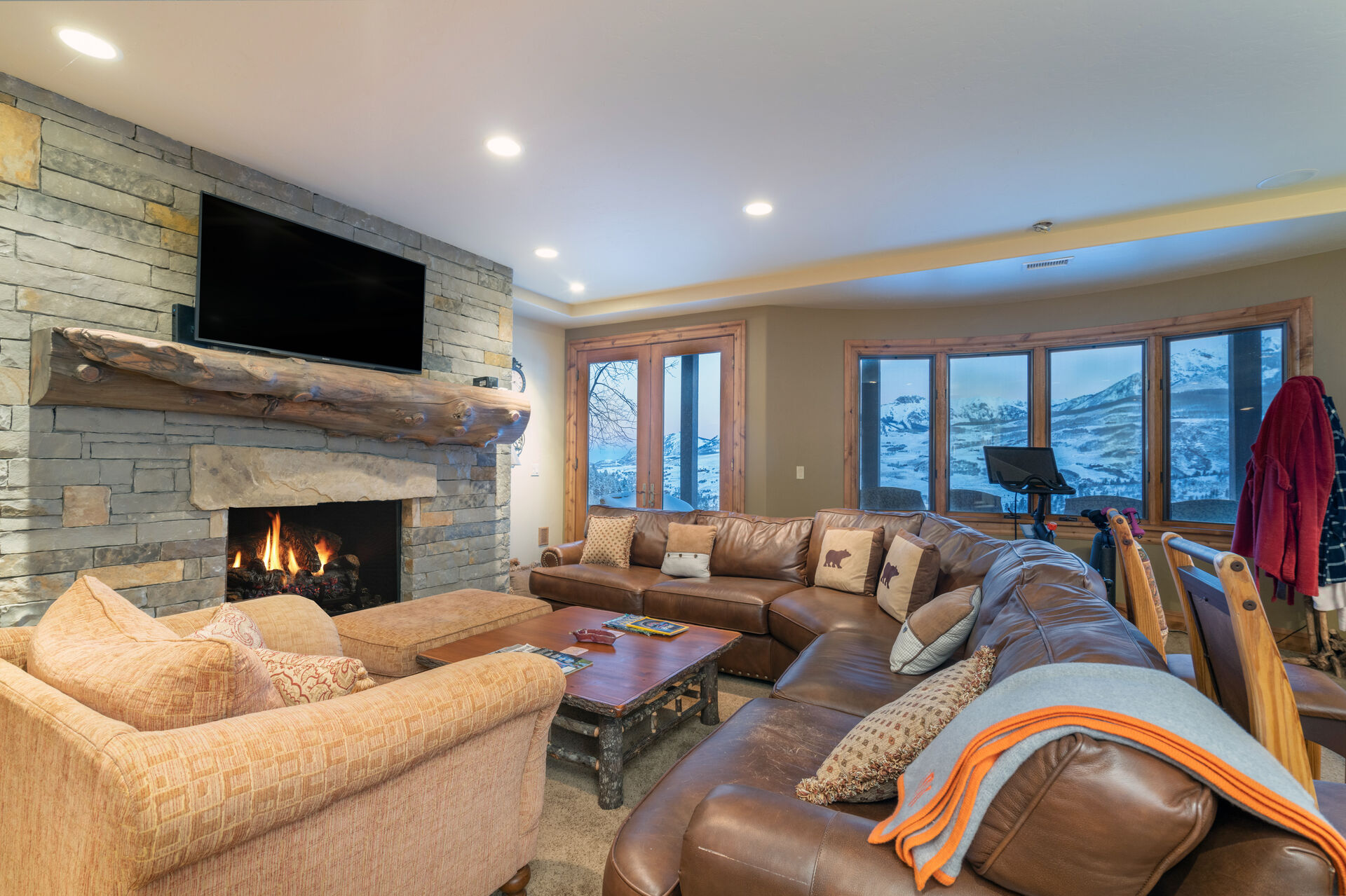 The living area of this Telluride golf rental is complete with a long sectional couch, armchair, fireplace, and TV.