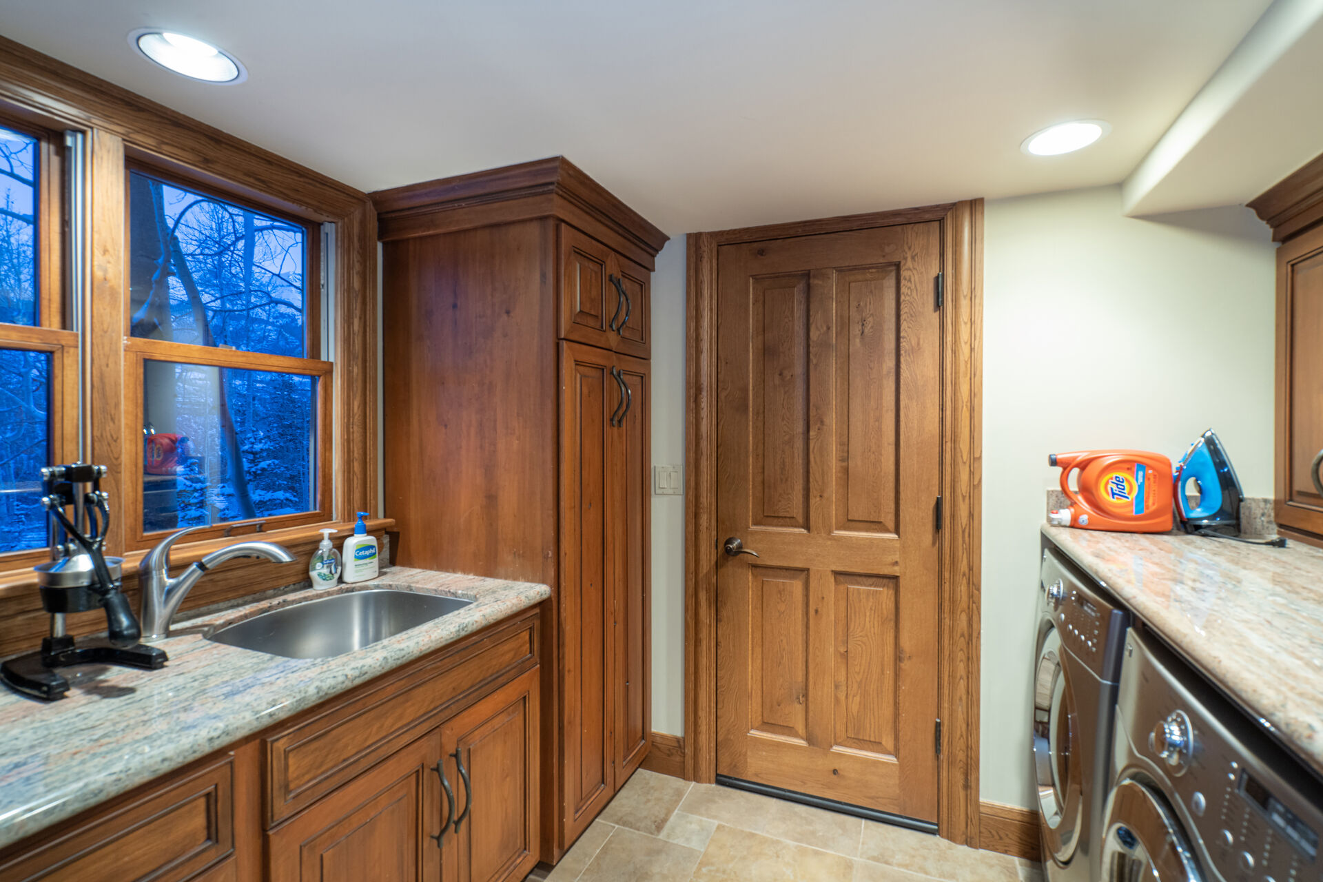Laundry room with sink and stainless steel washer and dryer.