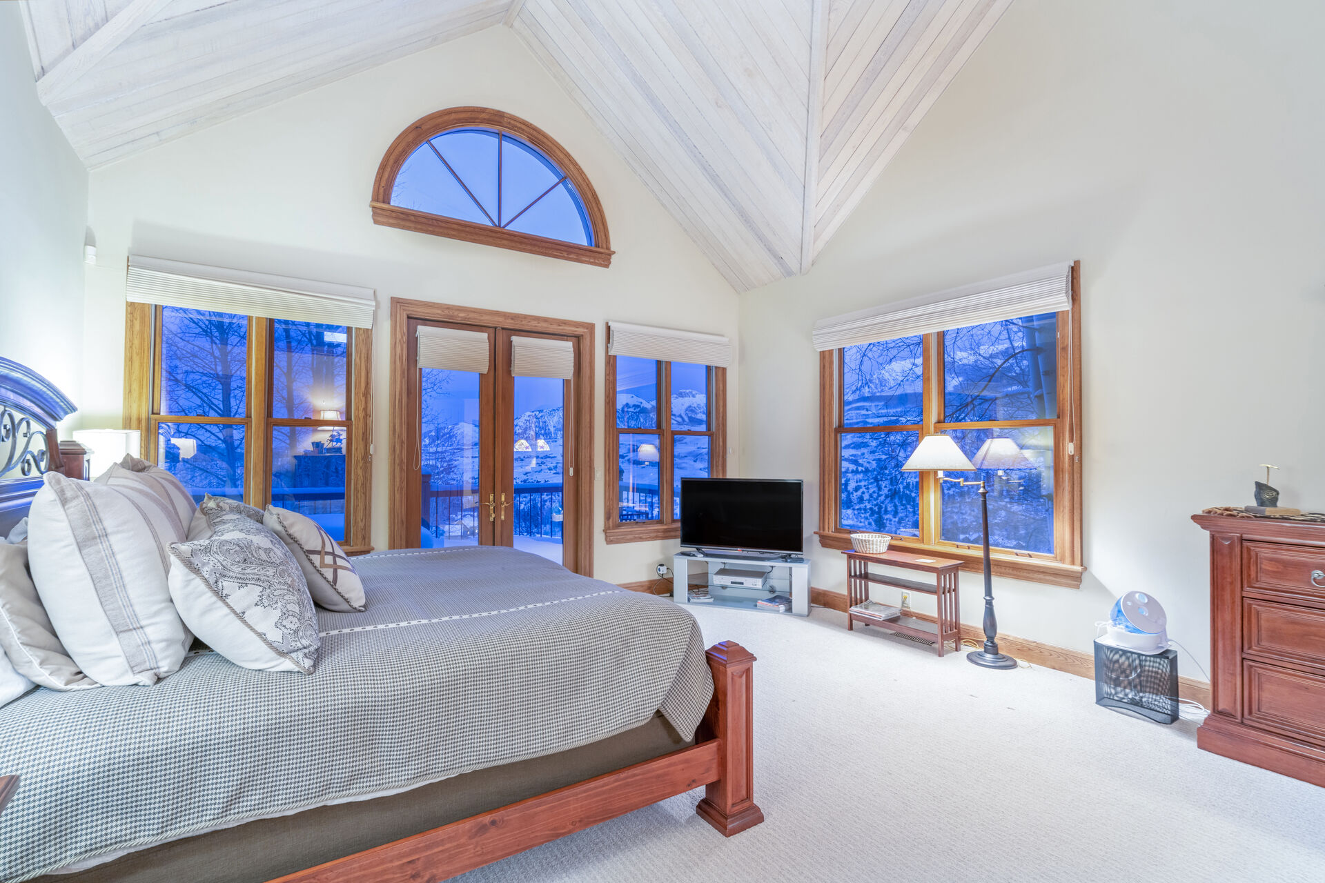 Master bedroom with ample floor space, flat-screen TV, and large bed, all surrounded by large windows.