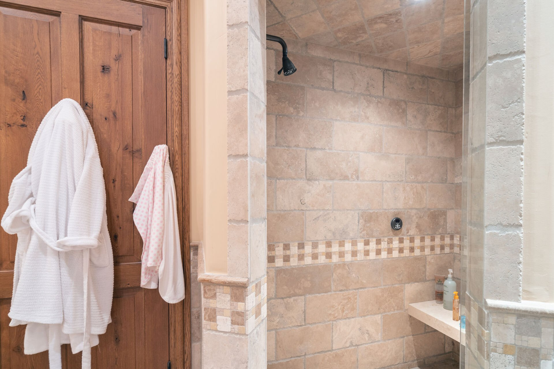 Walk-in shower with tile walls.