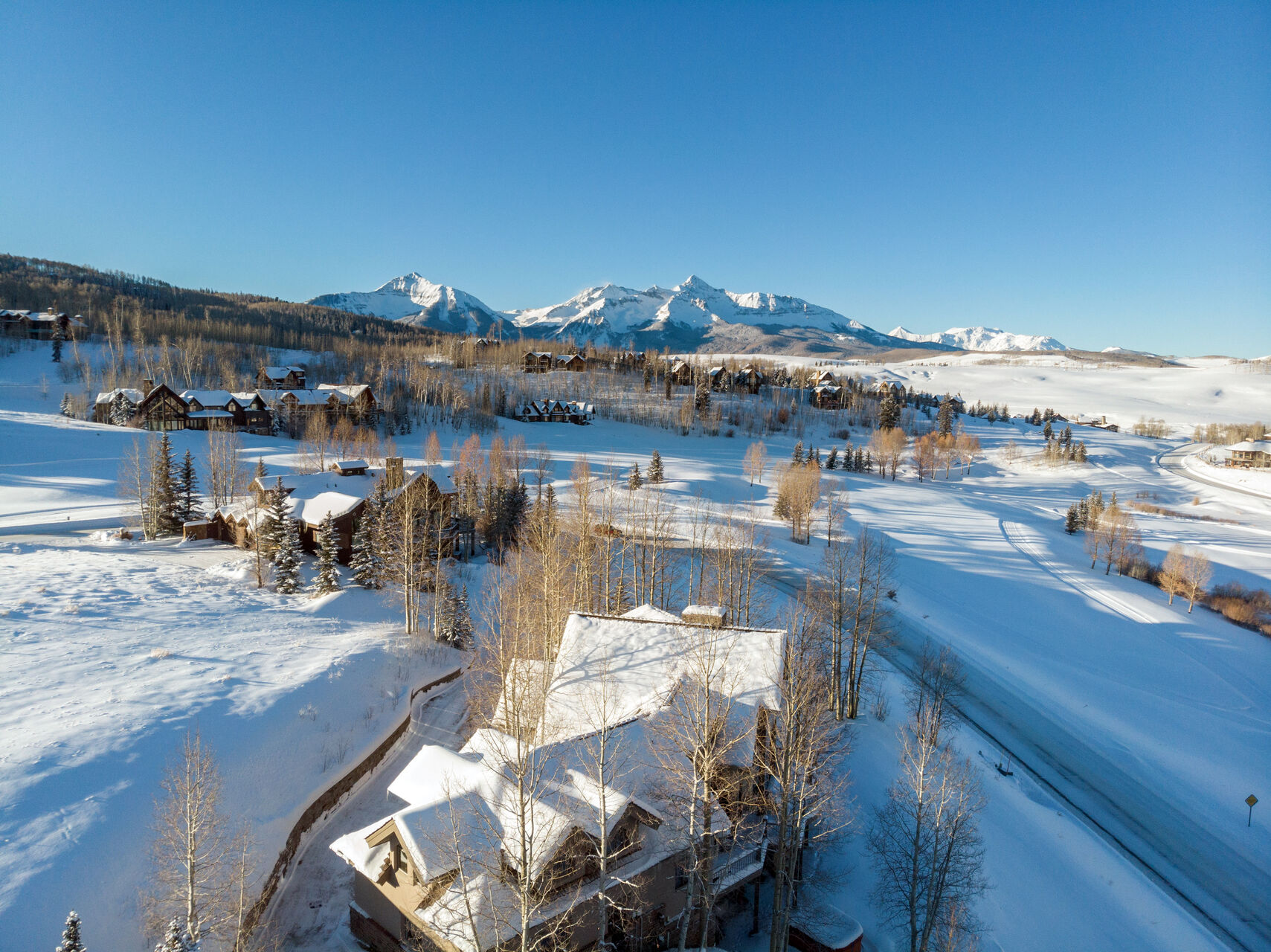 Aerial view of this Telluride golf rental and the surrounding area covered in snow.