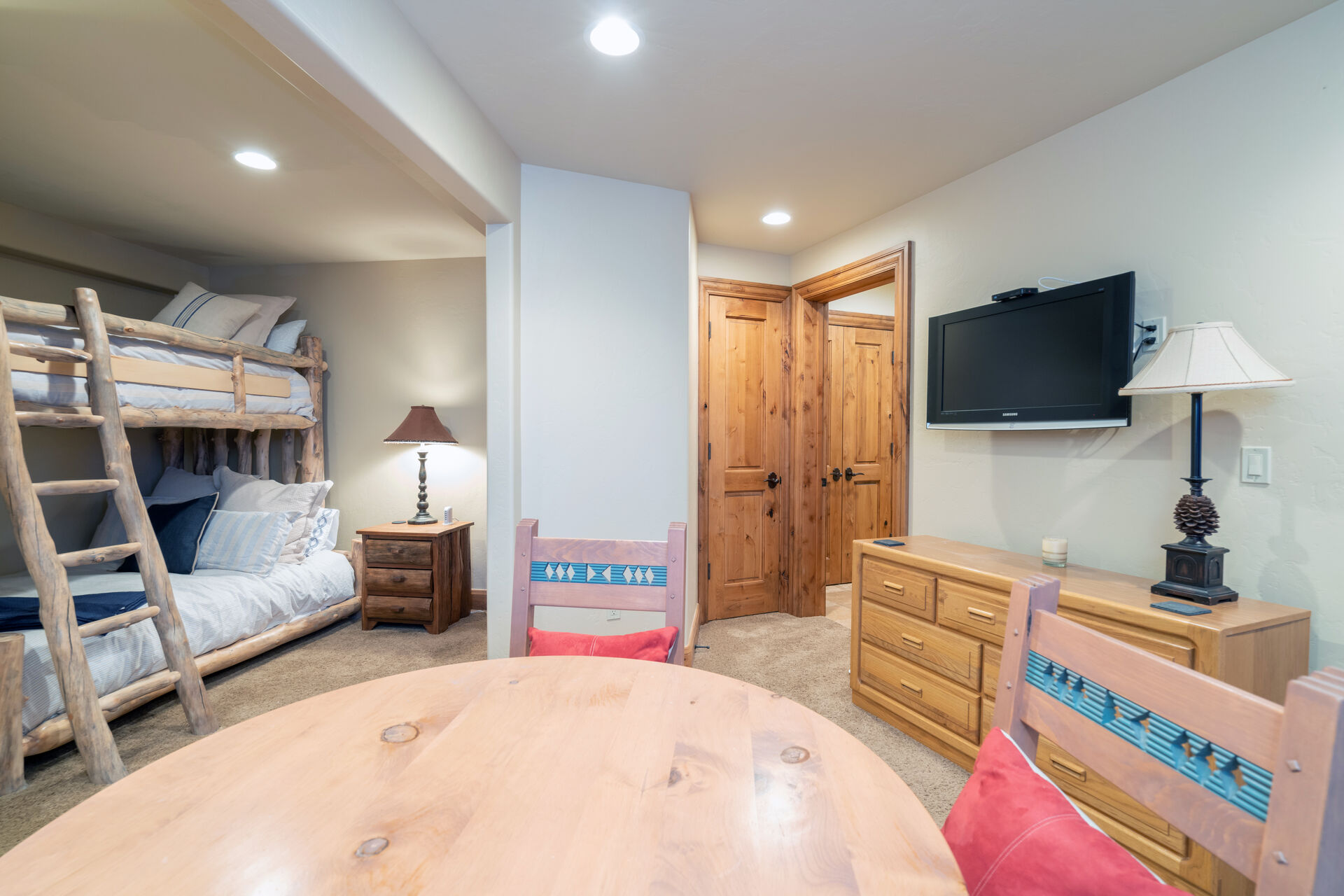 Large bedroom with table and seating, a bunk bed, and wall-mounted TV above a dresser.