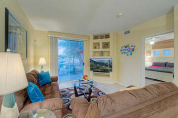 Comfortable great room has large TV and community lake view