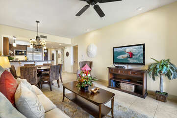 Wall-mounted TV sits above an entertainment center of the living room, in front of a coffee table and couch.
