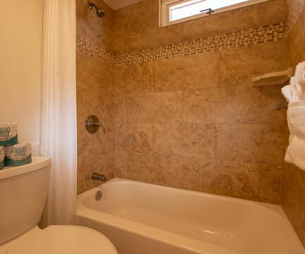 Fully tiled bath tub and shower area.