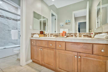 Hallway Bathroom for the whole family features a double vanity sink and combo shower/tub.