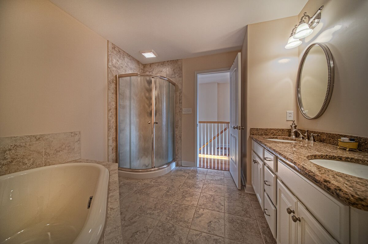 Bathroom with walk in shower and nearby tub