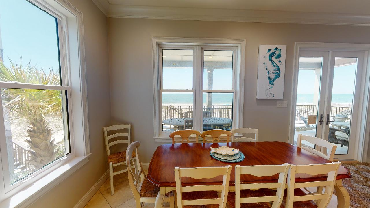Dining Table, Chairs, Windows, and Patio Doors to the Balcony.
