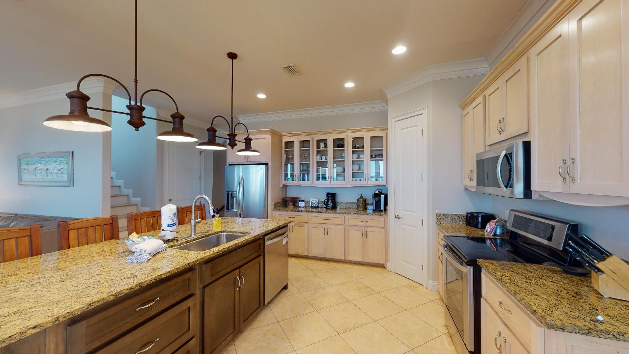 Kitchen with Counter, Stools, Ceiling Lamps, Refrigerator, and Microwave.