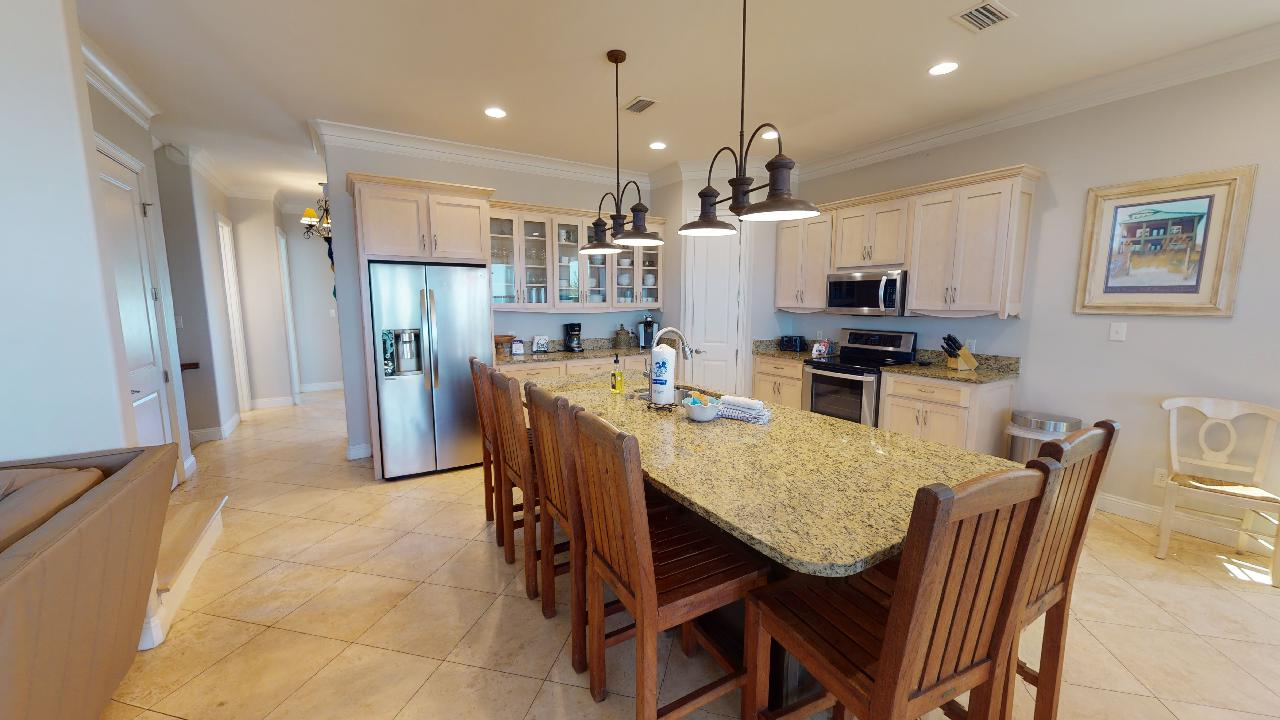 Kitchen Counter, Stools, Ceiling Lamps, Refrigerator, and Microwave.