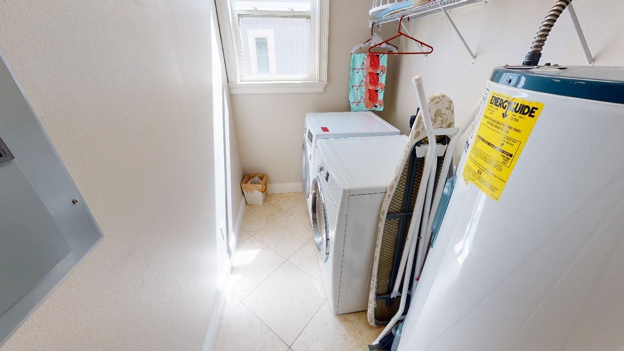 Laundry Room with Washer, Dryer, Water Heater, and Ironing Board.