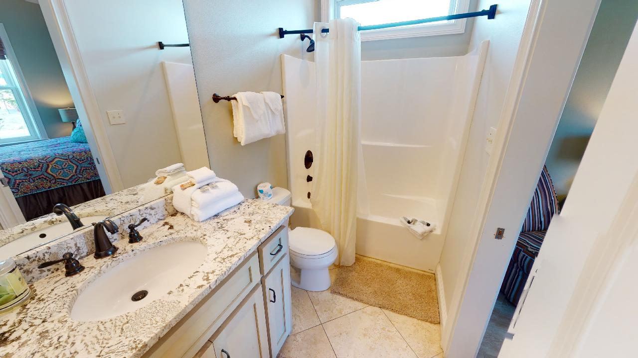 Bathroom with Shower-Tub Combo, Single Vanity Sink, Mirror, and Toilet.