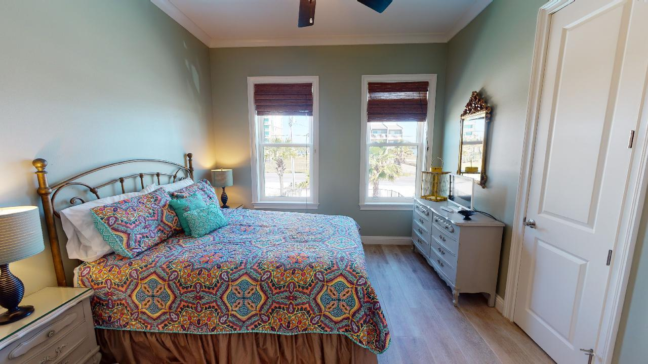 Large Bed, Windows, Drawer Dresser, Mirror, Lamps, and Nightstands.