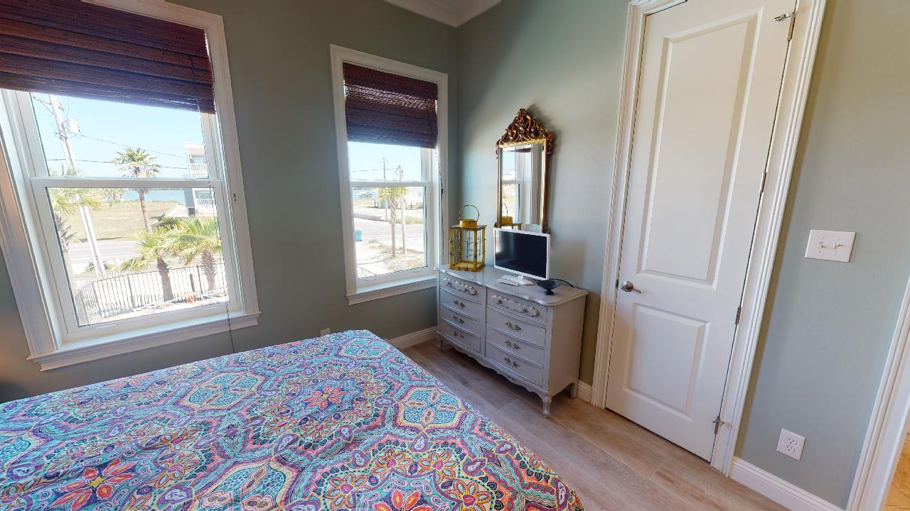 Large Bed, Windows, Drawer Dresser, Mirror, and TV.