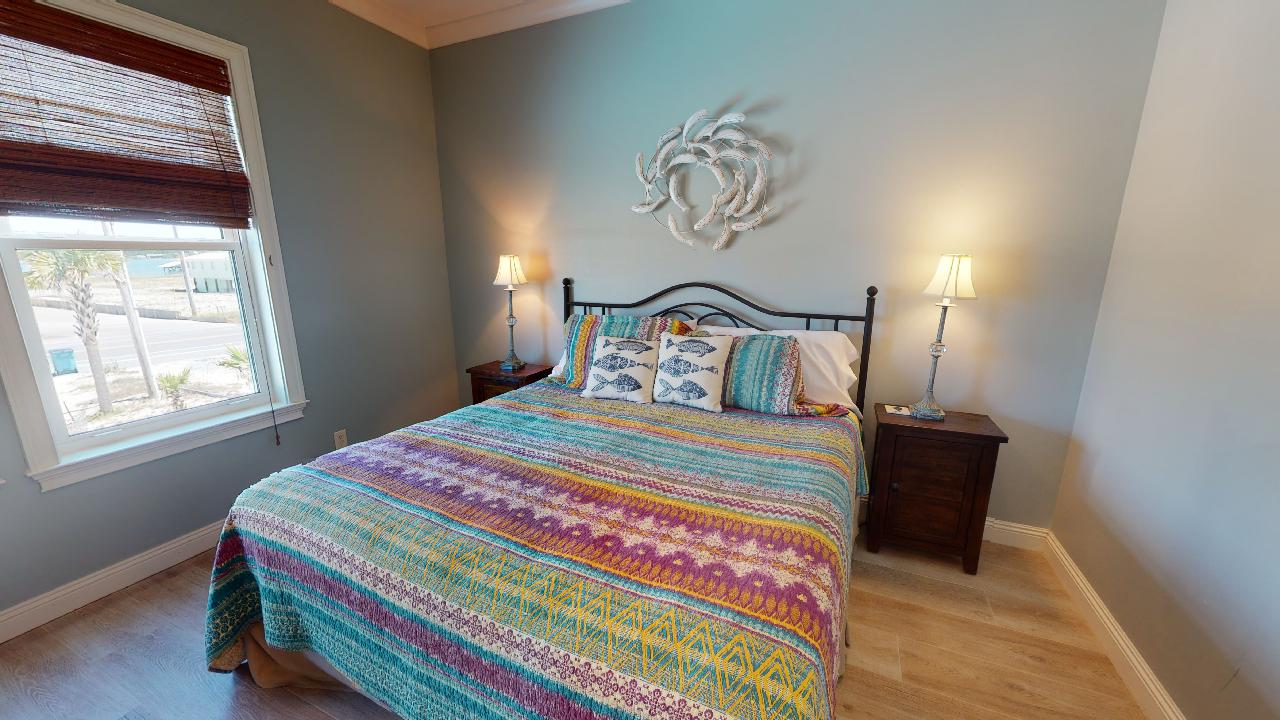 Bedroom with Large Bed, Nightstands, Table Lamps, and Window.