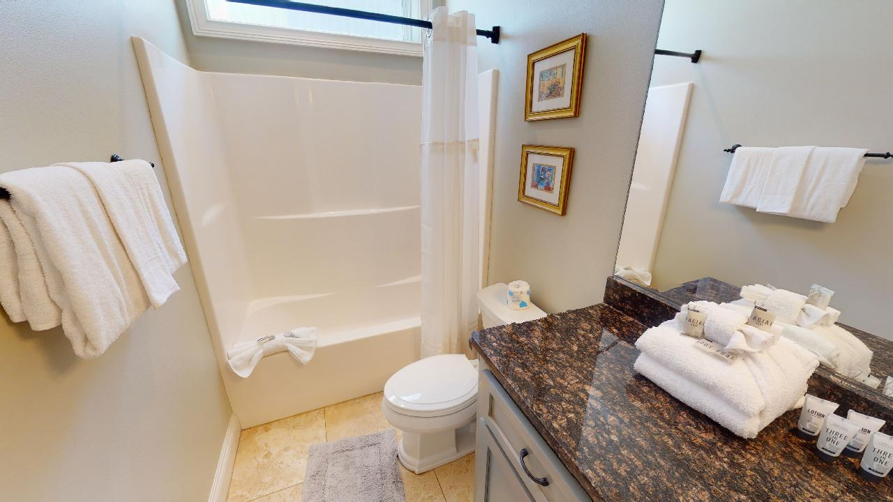 Bathroom with Shower-Tub Combo, Single Vanity Sink, and Toilet.
