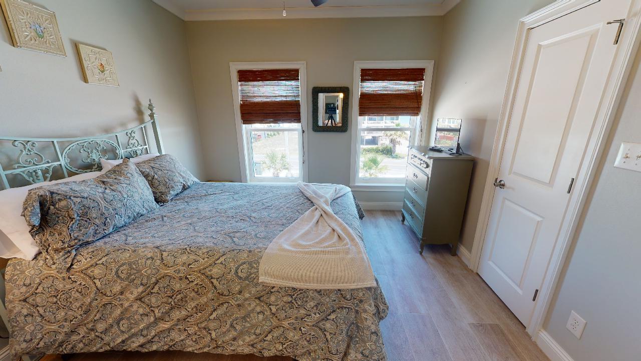 Large Bed, Dresser, TV, and Windows.