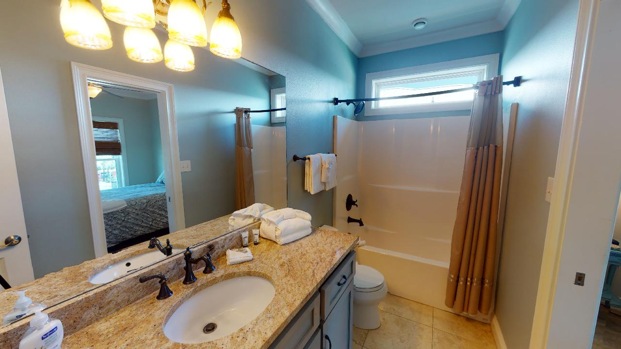 Shower-Tub Combo, Shower Curtain, Single Vanity Sink, Mirror, and Toilet.