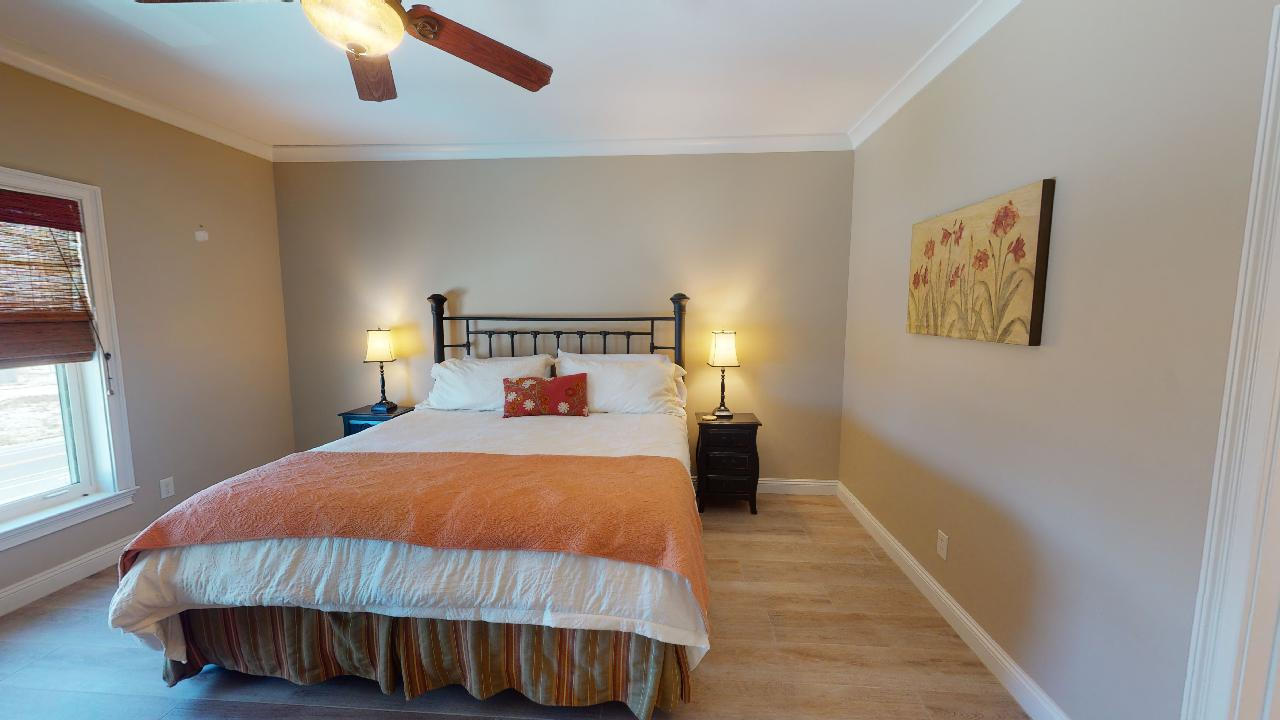 Large Bed, Window, Ceiling Fan, Table Lamps, and Nightstands.