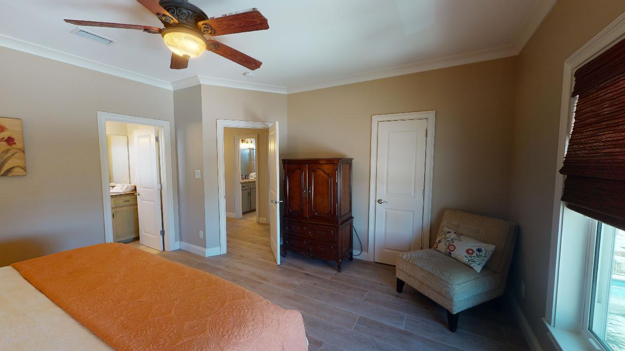 Large Bed, Window, Ceiling Fan, Arm Chair, and Wardrobe.