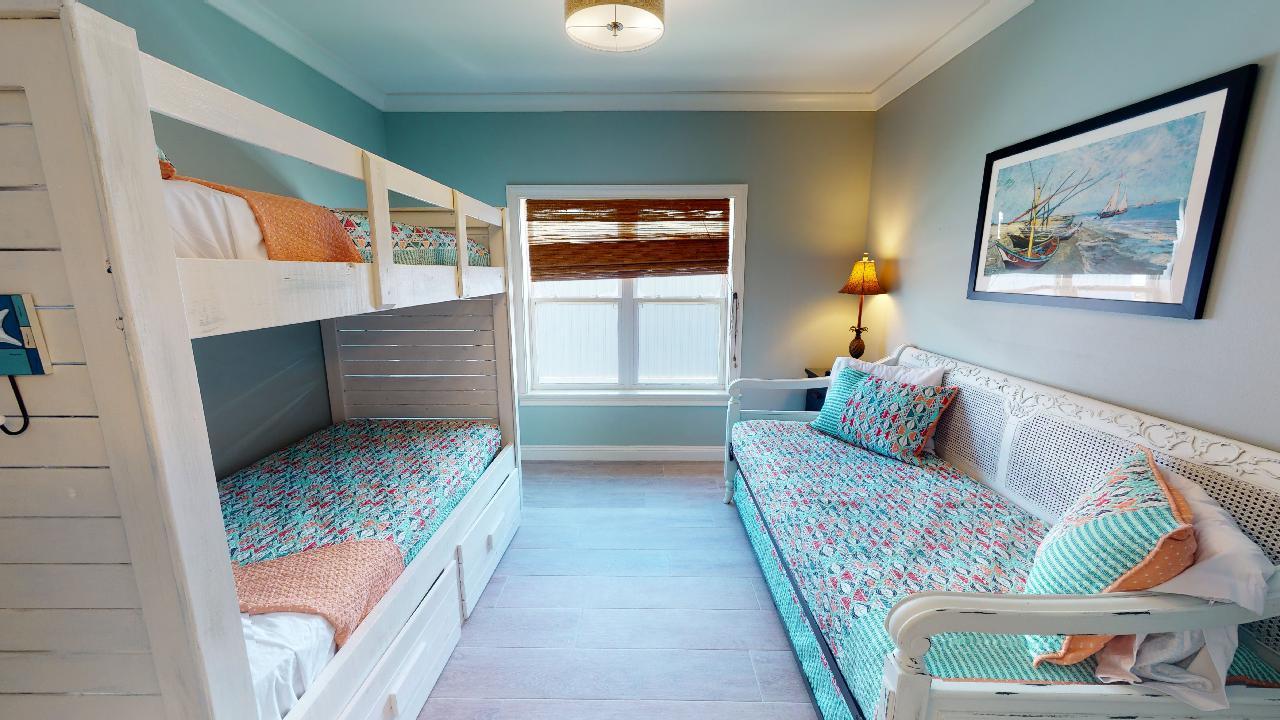 Bedroom with Bunker Bed, Sofa, Nightstand, Lamp, and Window.