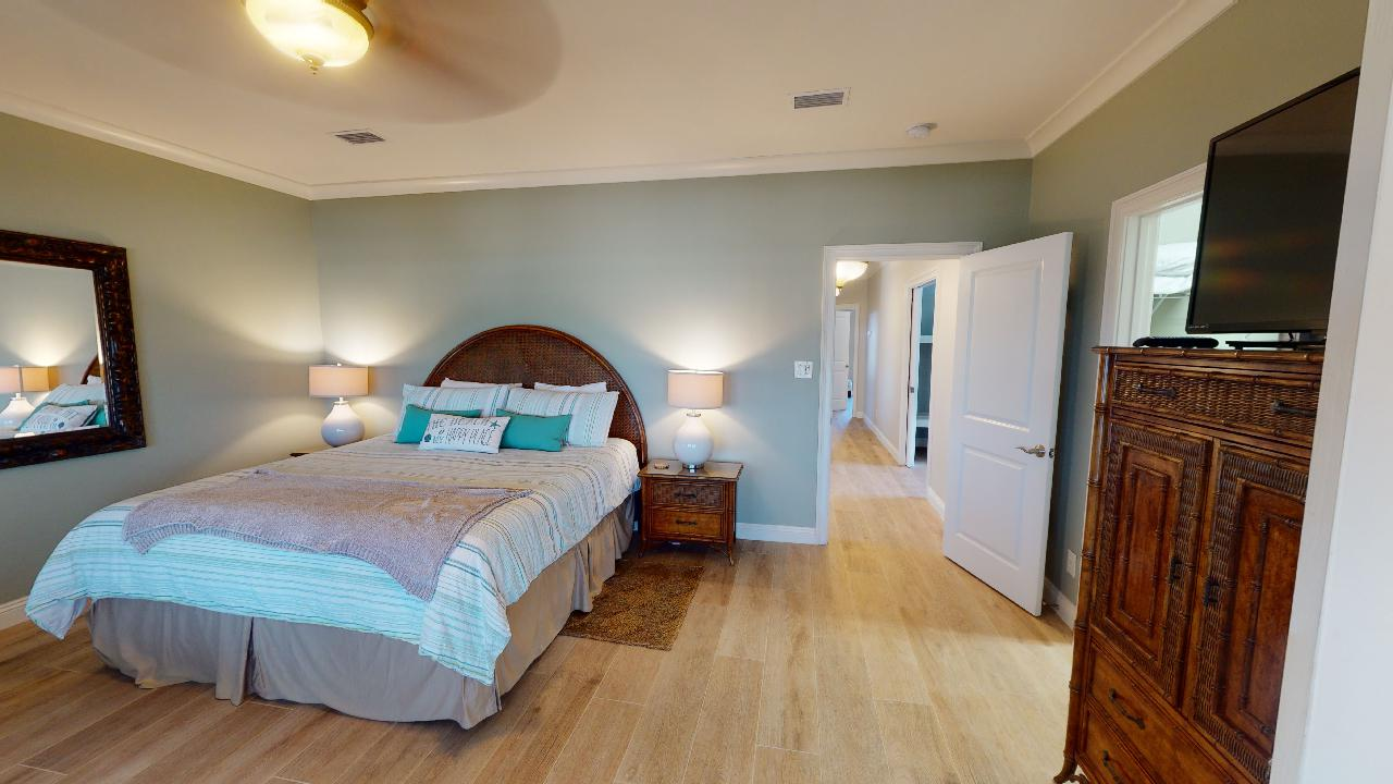 Bedroom with Large Bed, Dresser, TV, Nightstands, Lamps, and Mirror.