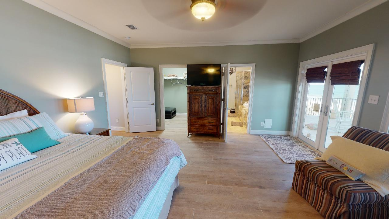 Large Bed, Dresser, TV, Nightstands, Patio Doors, and Arm Chair.