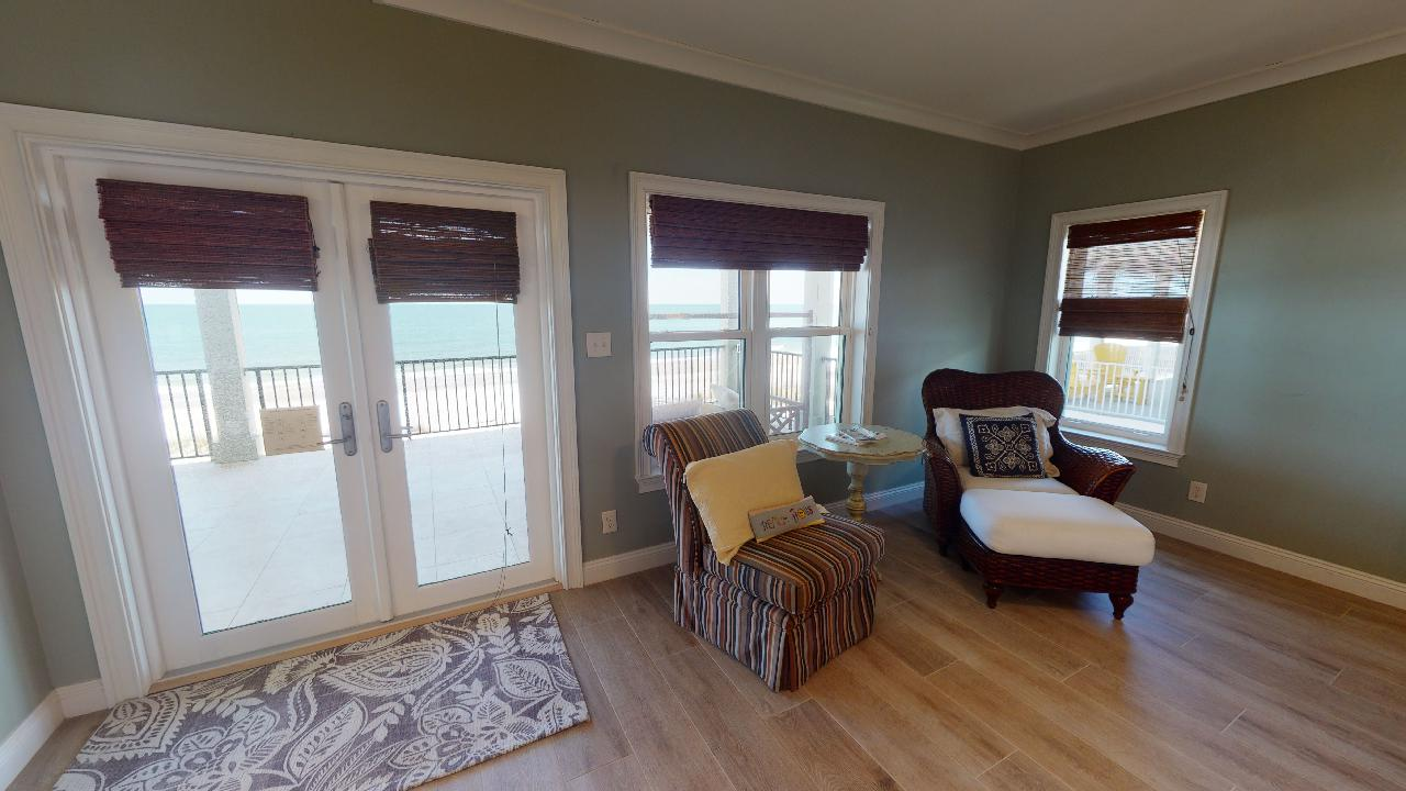 Arm Chairs in the Bedroom with Windows and Patio Doors.