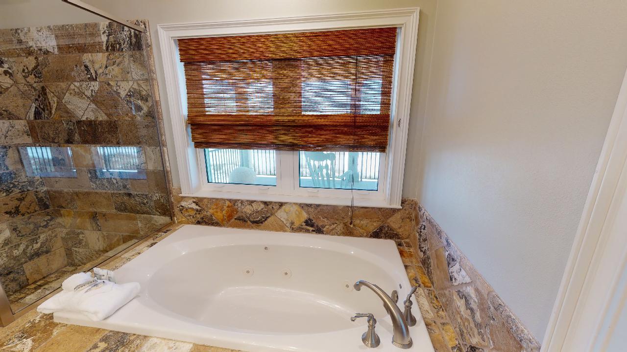 Bathtub and a Window to the Balcony.