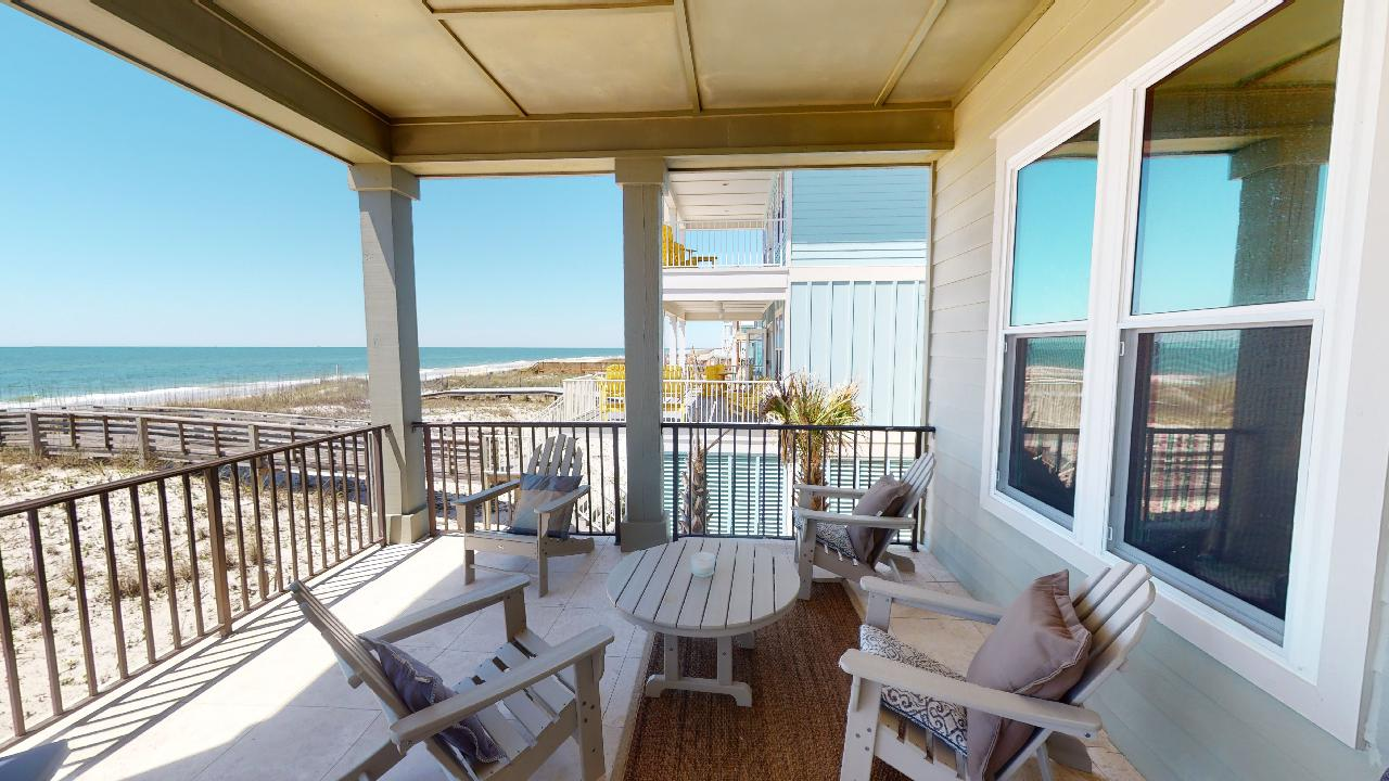 Big Balcony with Patio Chairs, Table, Windows, and a View of the Beach.