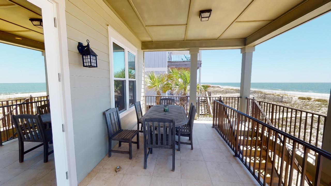 Big Balcony with Outdoor Dining Set, Windows, and the Staircase with Access to the Beach.